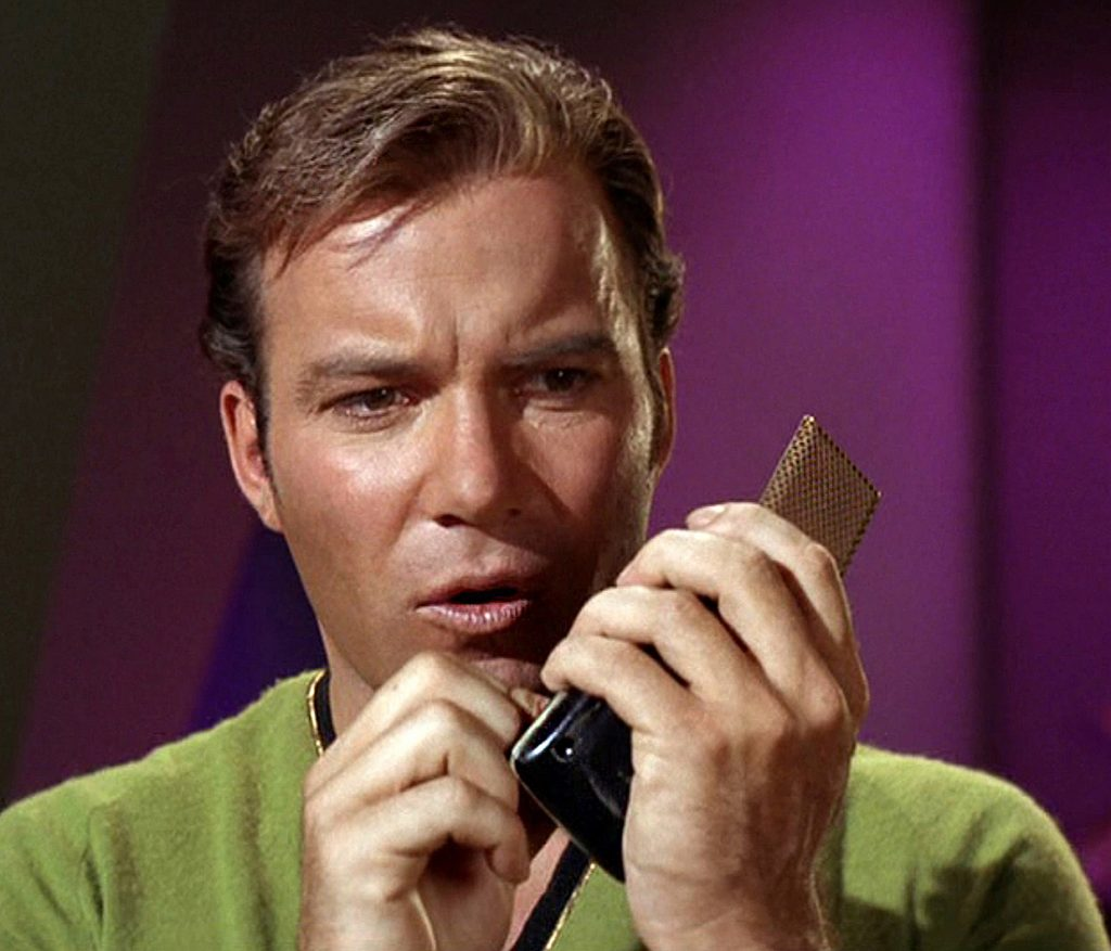 James Kirk with a hand-held communicator